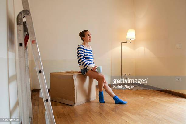 woman sitting on a box in her new, empty apartment