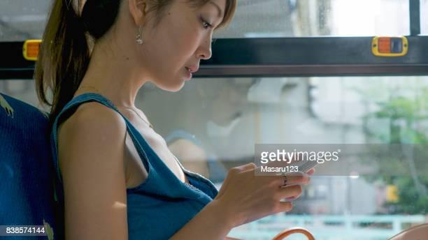 朝のバスで座っている女性