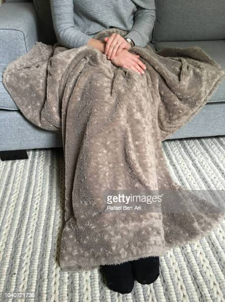 woman sitting on a caoch covered with warm blanket - rafael ben ari stock pictures, royalty-free photos & images