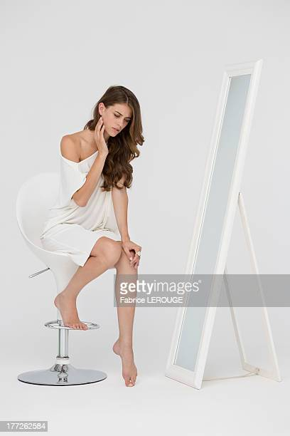 Woman sitting on a chair and checking her wrinkles