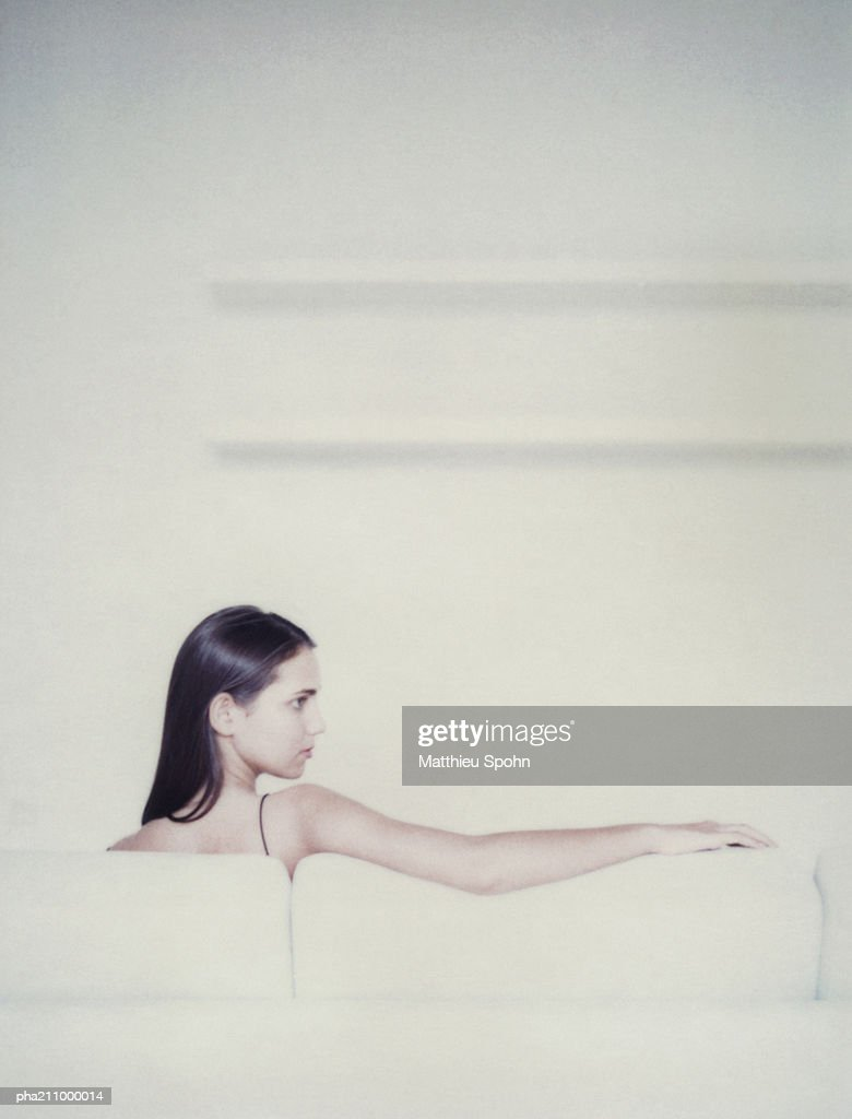 Woman sitting on a chair, rear view. : Stockfoto