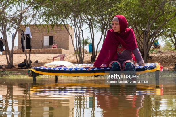 Woman sitting on a charpaï with her feet in the water on Avril 22, 2016 in Thatta, Sindh, Pakistan.