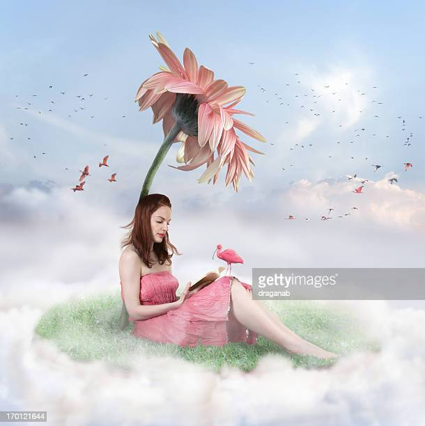 Woman sitting on a cloud with grass under a flower reading