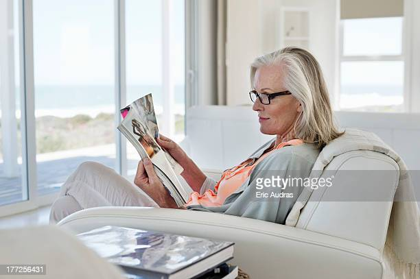 Woman sitting on a couch and reading a magazine at home