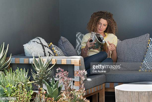 woman sitting on a couch and reading a magazine - magazine stock pictures, royalty-free photos & images