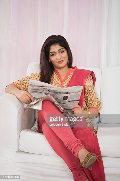 woman sitting on a couch and reading a newspaper - salwar kameez stock photos and pictures