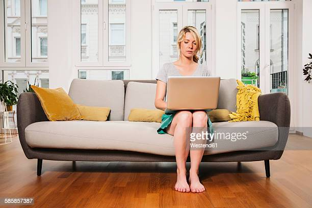 Woman sitting on a couch at living room using laptop
