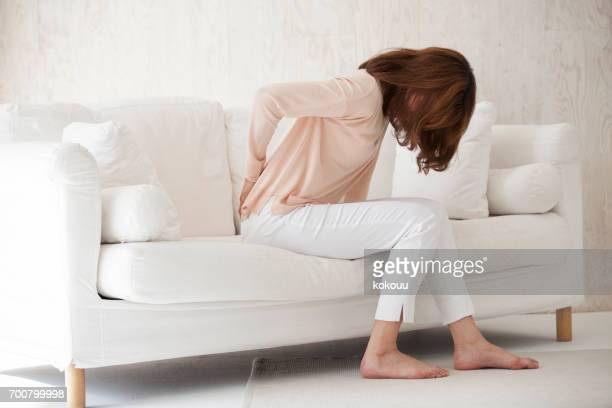 woman sitting on a couch - back pain stock pictures, royalty-free photos & images
