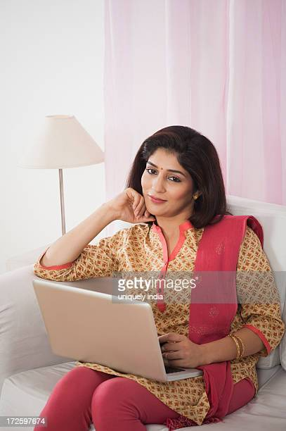 woman sitting on a couch with a laptop and day dreaming - salwar kameez stock pictures, royalty-free photos & images