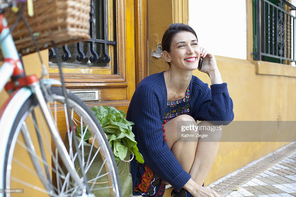 woman sitting on a doorstep, talking on the phone : Stock Photo