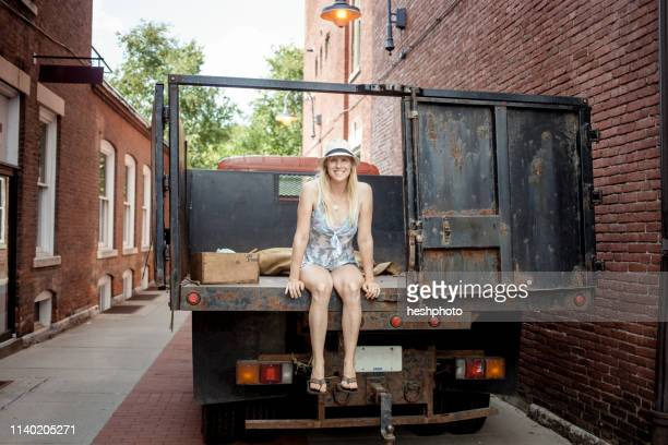 woman sitting on a farmer's organic food truck outside grocery store - heshphoto stock pictures, royalty-free photos & images