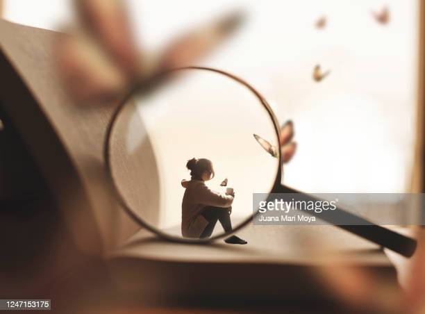 a woman sitting on a giant book having a cup of coffee.  she is dreaming of butterflies.  there is also a magnifying glass that is focusing on it. - literature stock pictures, royalty-free photos & images