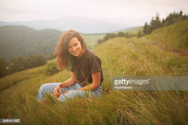 Woman sitting on a grass in the mountains