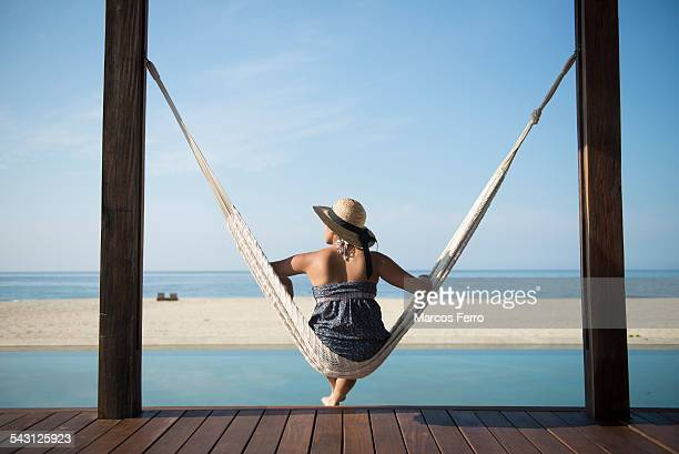 Woman sitting on a hamock at a small hotel in the coast of Oaxaca, Mexico.