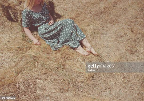 woman sitting on a hay bale - robe longue photos et images de collection