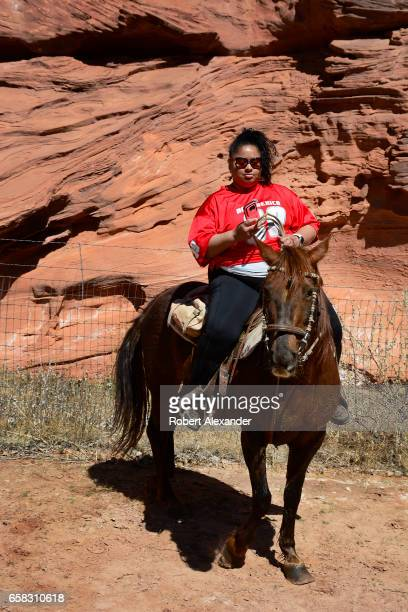 A woman sitting on a horse uses her smartphone to take a picture during a horseback tour at Canyon de Chelly National Monument near Chinle Arizona...
