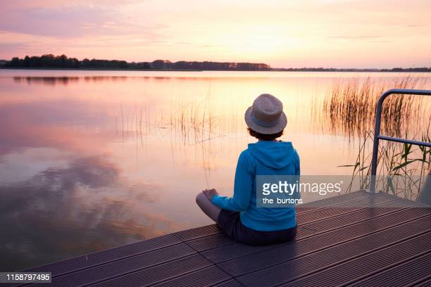 woman sitting on a jetty at an idyllic lake during sunset - bootssteg stock-fotos und bilder