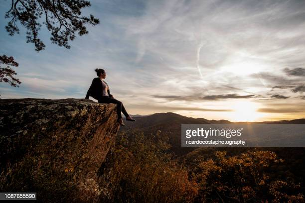 woman sitting on a landscape of skyline drive - virginia - usa - skyline drive virginia stock photos and pictures