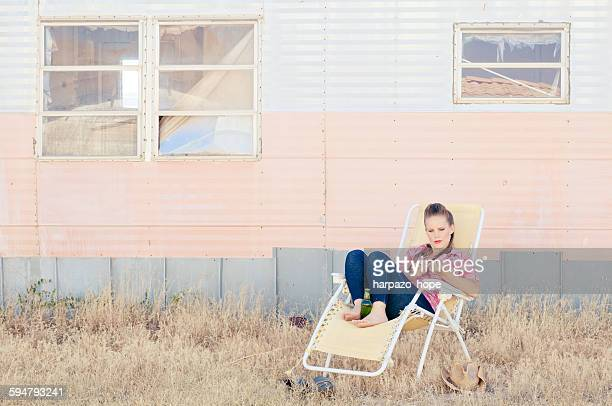 woman sitting on a lawn chair outside a trailer - redneck stock photos and pictures