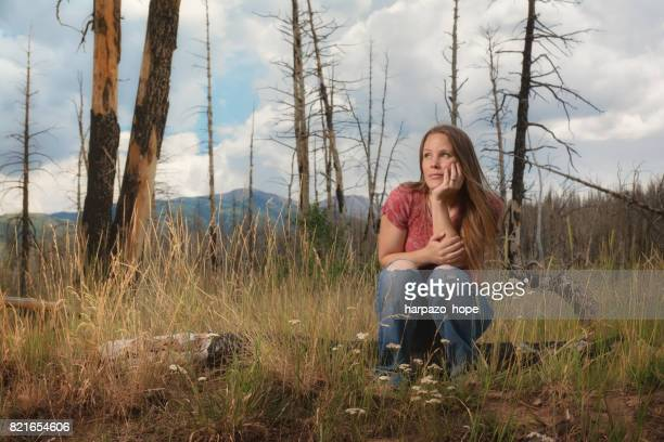 Woman Sitting on a Log in a Burnt Forest