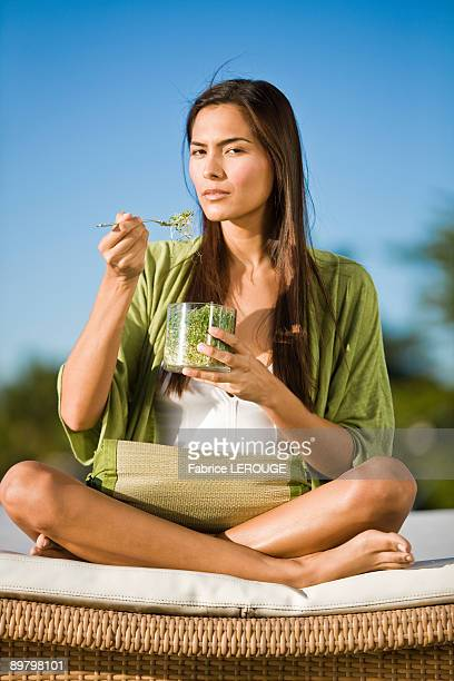 Woman sitting on a mattress and eating bean sprouts