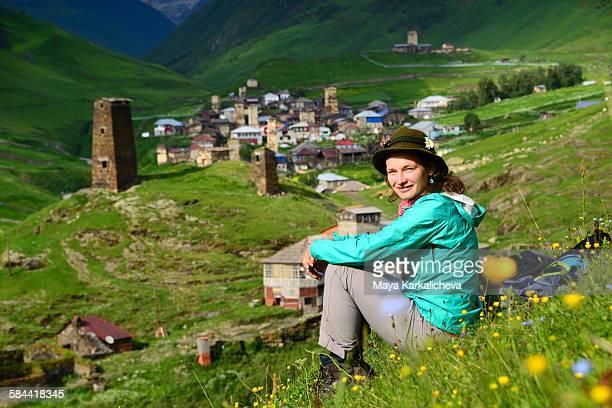woman sitting on a meadow in ushguli village - kaukasus geografische lage stock-fotos und bilder