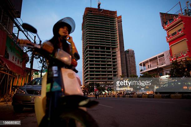 A woman sitting on a motorbike speaks on her mobile phone on Monivong Boulevard as the Gold Tower 42 project developed by Yon Woo Cambodia Co center...