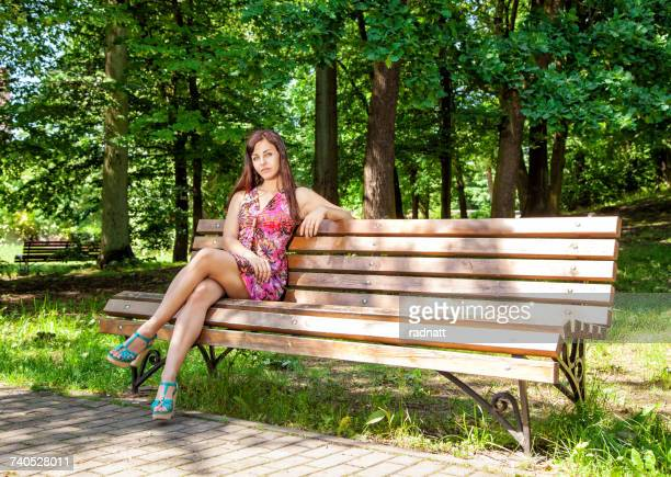 Woman sitting on a park bench in the sun