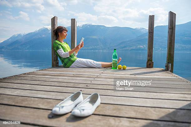 woman sitting on a pier - ascona stock pictures, royalty-free photos & images