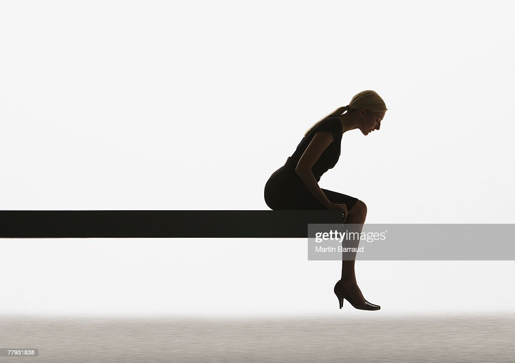 Woman sitting on a plank looking over ledge : Stock Photo