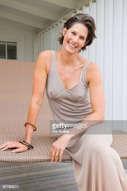 woman sitting on a porch swing and smiling - evening gown stock pictures, royalty-free photos & images