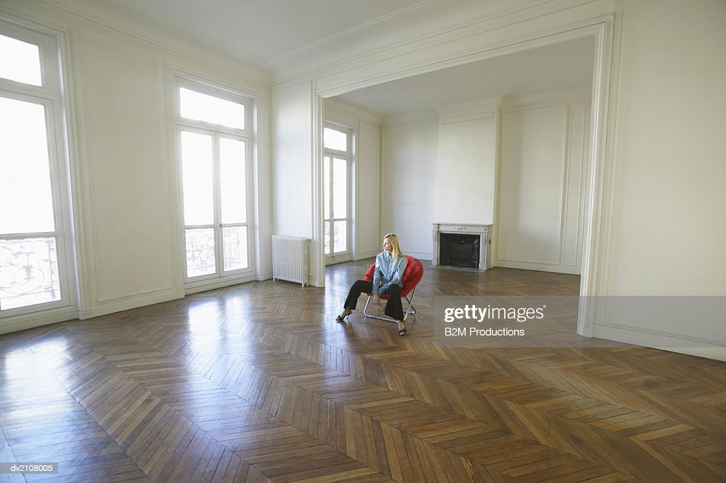 Woman Sitting on a Red Chair in a Large Empty Room : Stock Photo