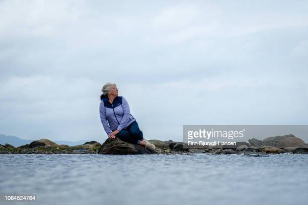 woman sitting on a rock at the seashore and the wind is blowing in her hair - finn bjurvoll stock photos and pictures