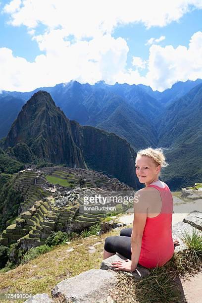 Woman sitting on a rock enjoying the view of Machu Picchu