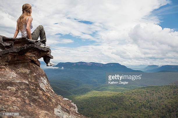 woman sitting on a rock, overlooking valley - blue mountains national park stock pictures, royalty-free photos & images
