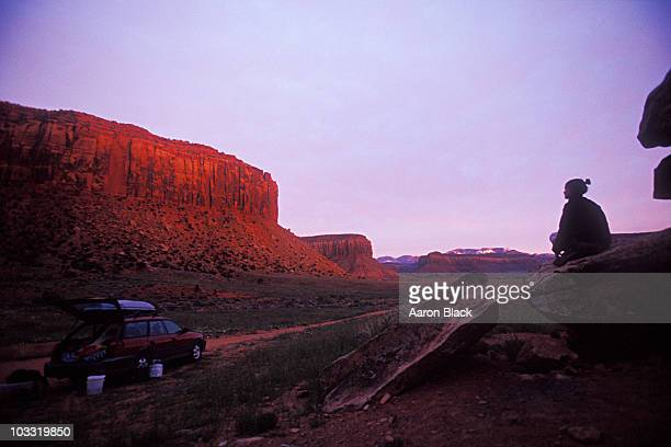 Woman sitting on a rock watches sun set on cliffs above her car.