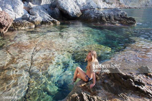 woman sitting on a rock with her feet in crystal clear water, ponza island, italy - mer tyrrhénienne photos et images de collection