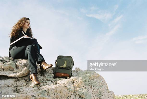 A woman sitting on a rock, writing in a notebook, a backpack lying by her feet.