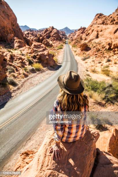 a woman sitting on a rocky point overlooking a scenic road leading through the desert. - las vegas stock pictures, royalty-free photos & images