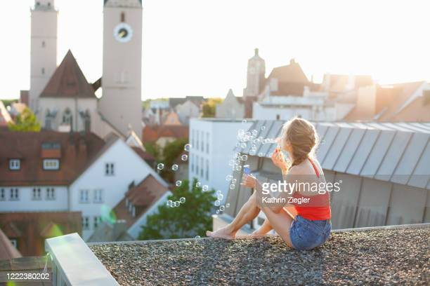 woman sitting on a rooftop, blowing soap bubbles - ホットパンツ ストックフォトと画像