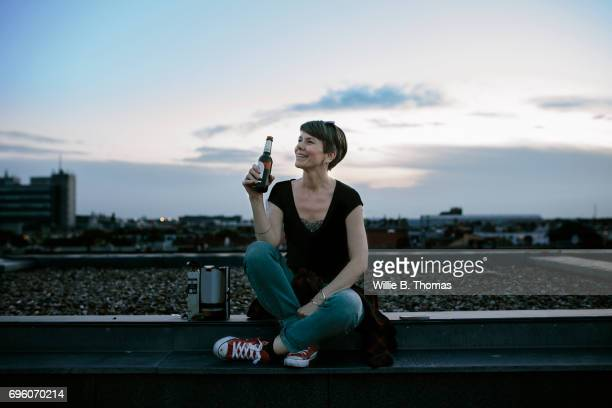 A Woman Sitting On A Rooftop Enjoying A Beer