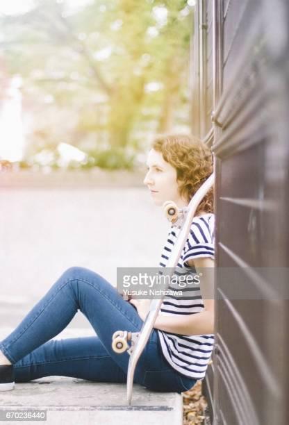 a woman sitting on a skateboard - yusuke nishizawa stock-fotos und bilder