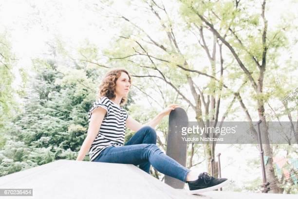 a woman sitting on a skateboard - yusuke nishizawa ストックフォトと画像