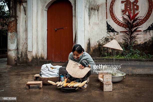 CONTENT] Woman sitting on a small wood stool in the streets of Cu Da to prepare grilled corn a traditionnal street food in Vietnam