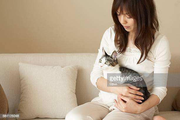 Woman sitting on a sofa and holding a pet cat