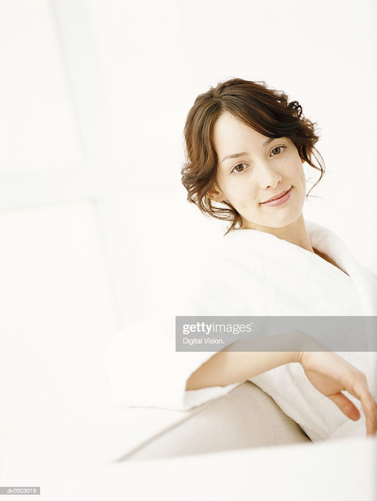 Woman Sitting on a Sofa in a Bathrobe : Stock Photo