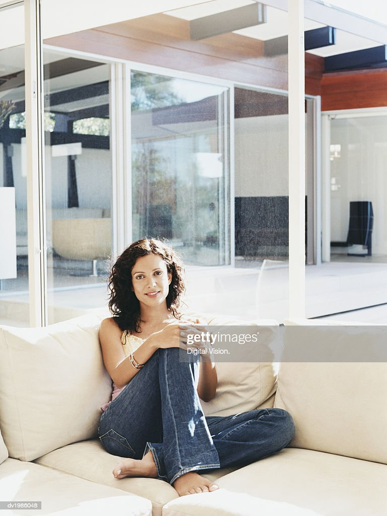 Woman Sitting on a Sofa in a Modern Living room : Stock Photo