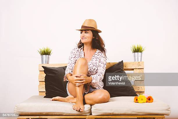 Woman sitting on a sofa in summer, Barcelona