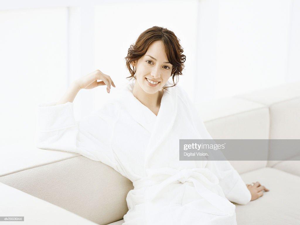 Woman Sitting on a Sofa Wearing a Bathrobe : Stock Photo