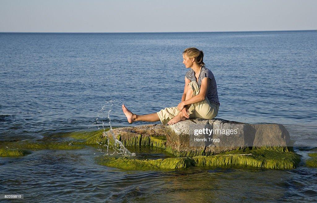 A woman sitting on a sunken rock Ostergotland Sweden. : Stock Photo